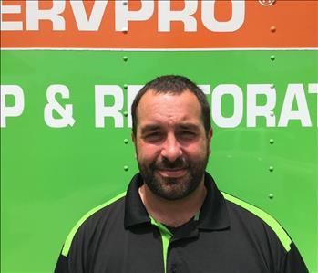 Operations Manager Chad Hobbs next to SERVPRO box truck at Norton Shores location